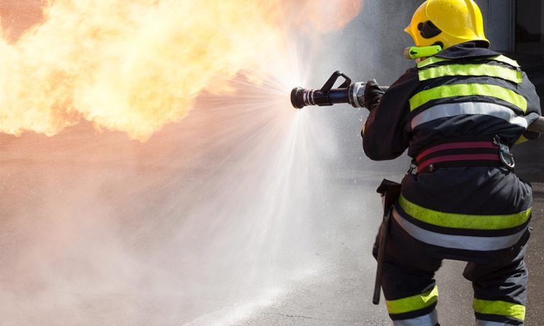 home –a rescue worker, dressed in a boiler suit, fighting a fire.
