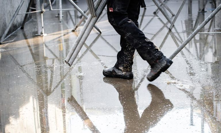 home –man, wearing safety boots, walking in the rain on a construction site.