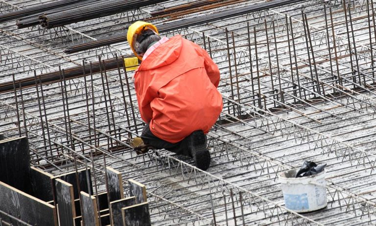 home – a construction worker on site, dressed in a rain jacket and hard hat.