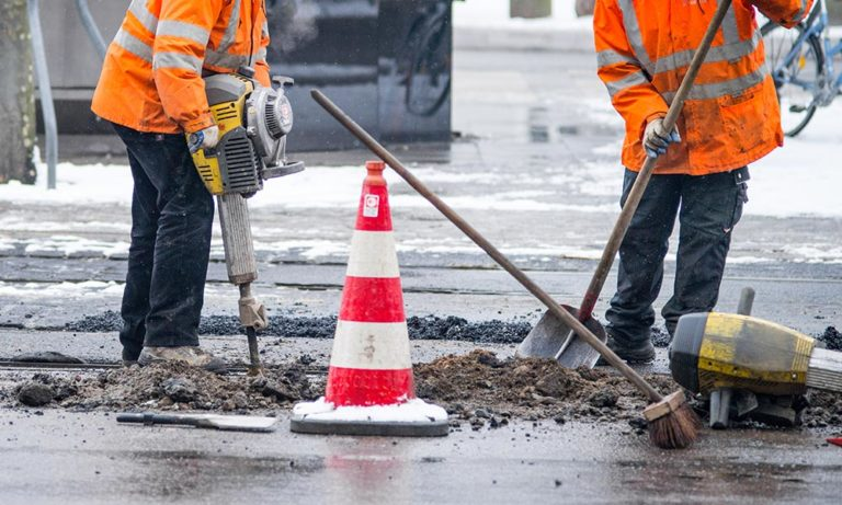 home –picture of a road construction workers dressed in workwear trousers.