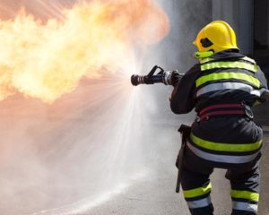 firefighter protective clothing –a rescue worker, dressed in a boiler suit, fighting a fire.