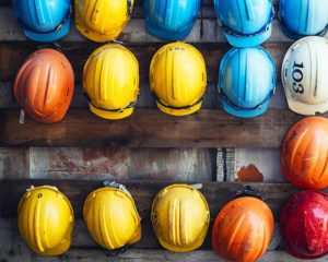 safety equipment suppliers – hard hats, in different colours, hanging from a wall.