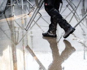 industrial shoes –man, wearing safety boots, walking in the rain on a construction site.