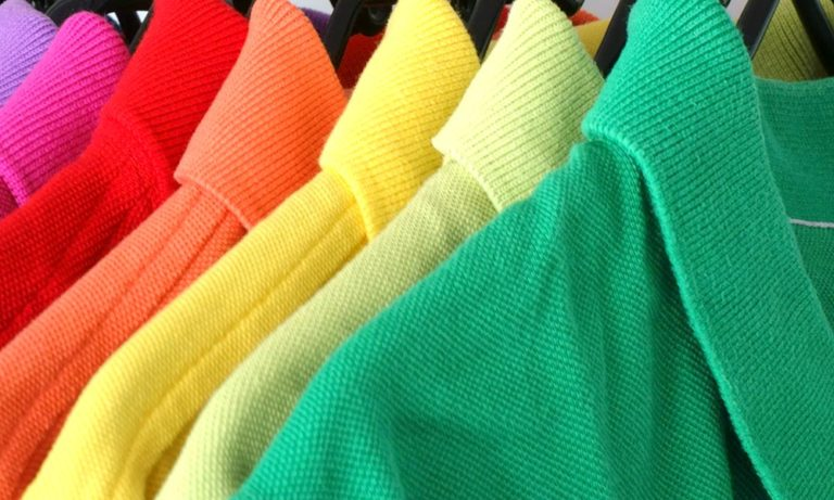 home –colourful golf shirts hanging in a row to illustrate the corporate branding solutions offered by Southern Workwear.